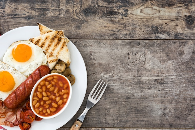 Tradycyjne pełne śniadanie angielskie ze smażonymi jajkami, kiełbasami, fasolą, pieczarkami, grillowanymi pomidorami i boczkiem na drewnianej tle kopii przestrzeni