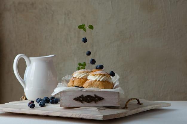 Tradycyjne pieczone domowe bułeczki ze śmietaną na śniadanieszwedzki chleb semla na czwartek throve