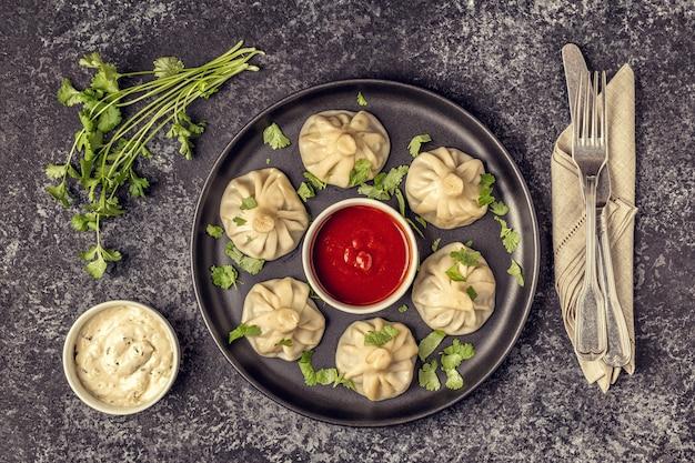 Tradycyjne pierogi gotowane na parze khinkali z sosem pomidorowo-tatarskim