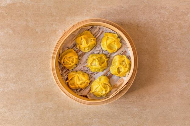 Tradycyjne pierożki manti gotowane na parze w drewnianym garnku.