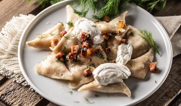 Tradycyjne polskie, ukraińskie lub słowackie danie na pierogi z kwaśną śmietaną, boczkiem i koperkiem.