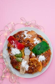Tradycyjne portugalskie ciasto owocowe bolo rei na różowym tle