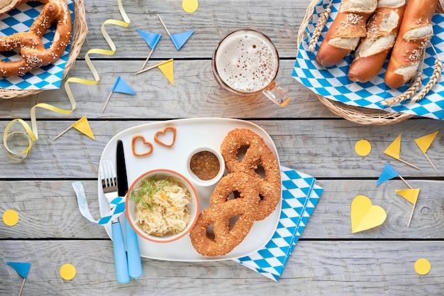 Tradycyjne potrawy oktoberfest i piwo na zdobionym drewnianym stole. precle leberwurst z kiszoną kapustą, precle chlebowe i paluszki.