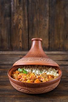 Tradycyjne potrawy tajine, kuskus i świeża sałatka na rustykalnym drewnianym stole.