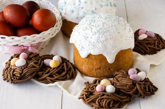 Tradycyjne potrawy wielkanocne. ciasta, ciasteczka gniazdowe i kolorowe jajka na drewnianym stole.