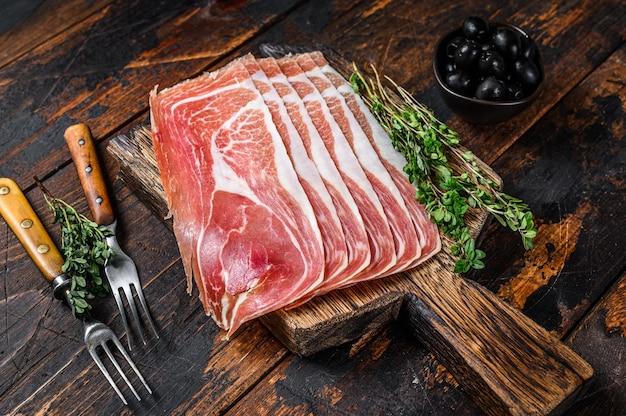 Tradycyjne prosciutto crudo, szynka parmeńska, włoskie antipasto na desce do krojenia. ciemny drewniany stół. widok z góry.