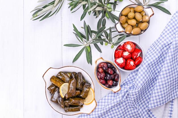 Tradycyjne przekąski, oliwki z kuchni greckiej. białe tło drewna. widok z góry. świeże gałęzie oliwek. skopiuj miejsce
