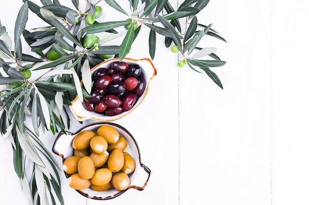 Tradycyjne przekąski, zielone i czerwone oliwki z kuchni greckiej. białe tło drewna. świeże gałęzie oliwek. skopiuj miejsce
