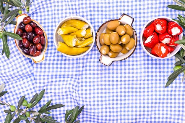 Tradycyjne przekąski, zielone i czerwone oliwki z kuchni greckiej. świeże gałęzie oliwek. copyspace. powyżej. obrus w kratkę w kolorze niebieskim