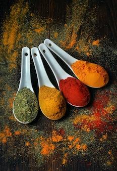 Tradycyjne przyprawy. papryczka chili, kurkuma, curry i suchy koperek w łyżkach na stole. widok z góry