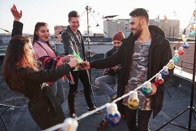 Tradycyjne pukające okulary. żarówki w całym miejscu na dachu, gdzie młoda grupa przyjaciół postanowiła spędzić weekend z gitarą i alkoholem