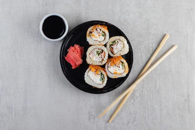 Tradycyjne roladki sushi ozdobione chrupiącymi frytkami na czarnym talerzu.