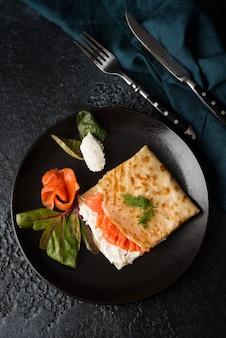 Tradycyjne rosyjskie cienkie naleśniki z nadzieniem, czerwoną rybą i serem śmietankowym, widok z góry