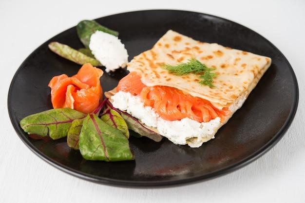 Tradycyjne rosyjskie cienkie naleśniki z nadzieniem, czerwoną rybą i serem śmietankowym, z bliska