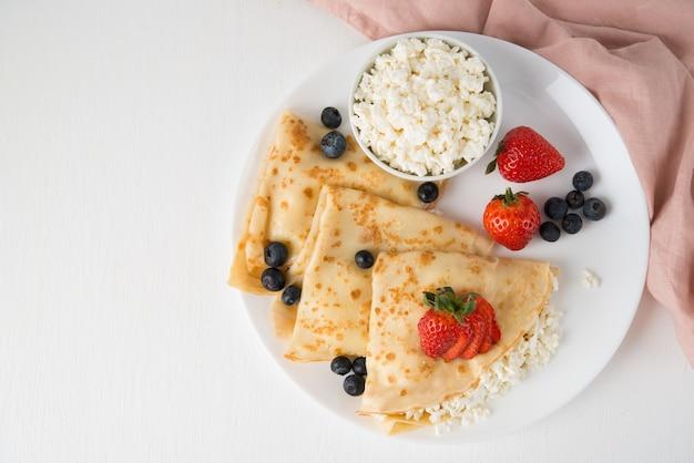 Tradycyjne rosyjskie cienkie naleśniki z serem i jagodami na talerzu na białym, widok z góry, kopia przestrzeń