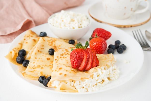 Tradycyjne rosyjskie cienkie naleśniki z serem i jagodami w talerzu na białym, bliska, selektywne fokus
