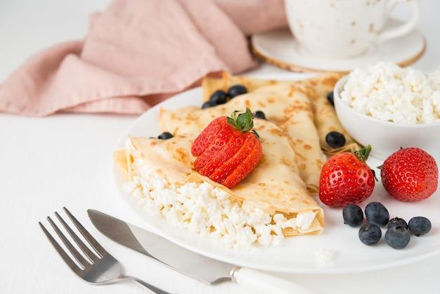 Tradycyjne rosyjskie cienkie naleśniki z serem i jagodami w talerzu na białym, selektywnym fokusie, kopia przestrzeń