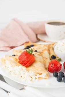 Tradycyjne rosyjskie cienkie naleśniki z serem i jagodami w talerzu na białym