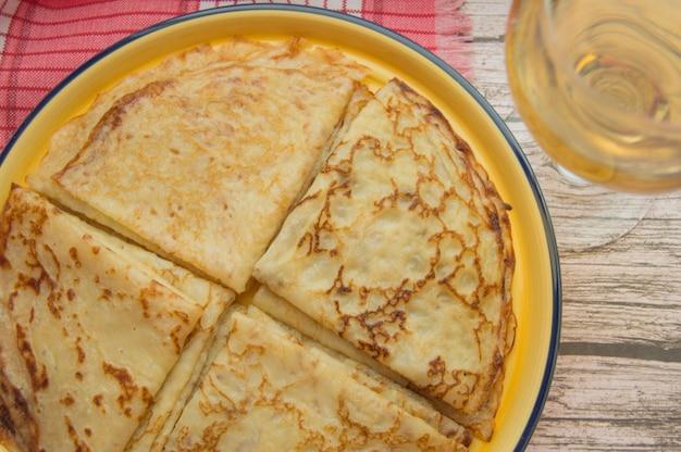 Tradycyjne rosyjskie jedzenie, pyszne naleśniki na talerzu, ułożone w stos.