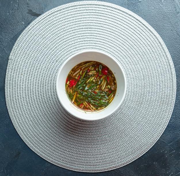 Tradycyjne rosyjskie lato okroshka zupa zimna z kwasem w misce na drewniane tła. widok z góry.