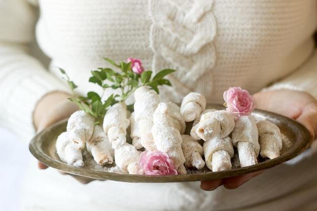 Tradycyjne rumuńskie lub mołdawskie ciasteczka kruche z nadzieniem dżemowym na tacy w rękach kobiet.