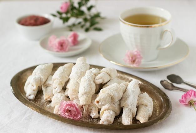 Tradycyjne rumuńskie lub mołdawskie ciasteczka kruche z nadzieniem z dżemu i filiżanką herbaty na jasnym tle.