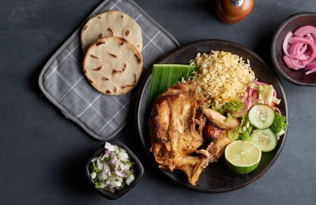 Tradycyjne salwadorskie danie pieczona kura podawana z ryżem, cytryną, cebulą i tortillami kukurydzianymi, kuchnia ameryki łacińskiej