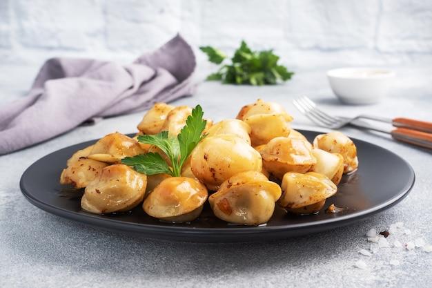 Tradycyjne smażone pelmeni, ravioli, pierogi z mięsem na czarnym talerzu, kuchnia rosyjska. szary betonowy stół, miejsce na kopię.