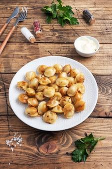 Tradycyjne smażone pelmeni, ravioli, pierogi z mięsem na talerzu, kuchnia rosyjska. drewniany stół rustykalny, miejsce na kopię.