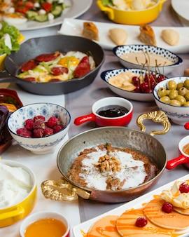 Tradycyjne śniadanie azerbejdżańskie z kakao, kiełbasą i jajkiem, naleśnikiem, sałatką