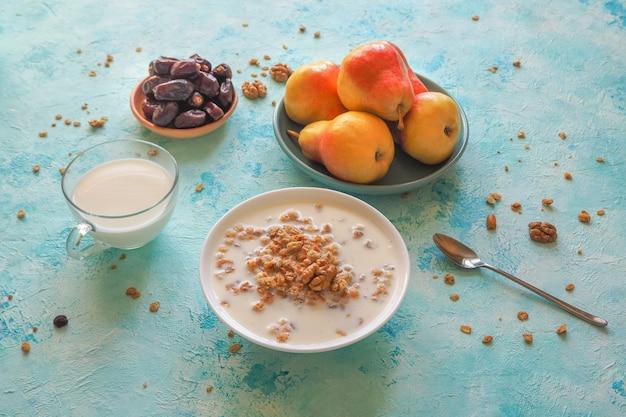 Tradycyjne śniadanie europejskie. mleko i muesli musli, daktyle i świeże gruszki.