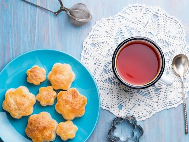Tradycyjne śniadanie z filiżanką herbaty i słodkich wypieków. talerz bułeczek,