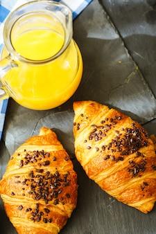 Tradycyjne śniadanie z rogalikami i sokiem pomarańczowym