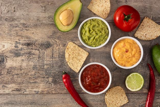 Tradycyjne sosy meksykańskie. guacamole, sos chili i sos serowy na drewnianym stole
