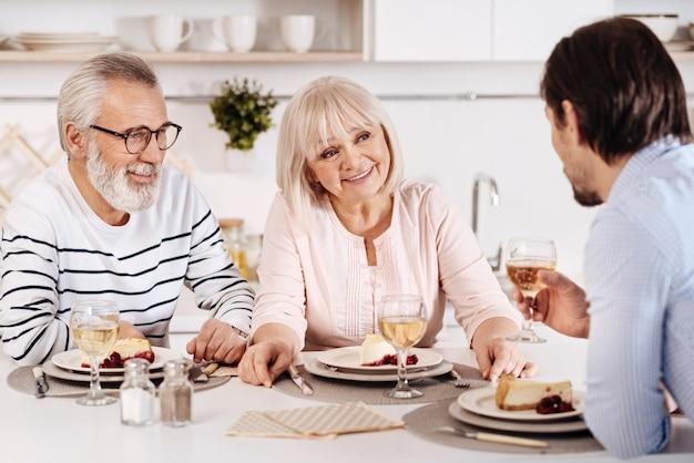 Tradycyjne spotkanie rodzinne. optymistyczna szczęśliwa śliczna starsza para je obiad i cieszy się wakacjami ze swoim dojrzałym synem podczas rozmowy