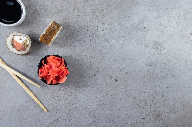 Tradycyjne sushi rolki z tuńczykiem i marynowanym imbirem na kamiennym tle.