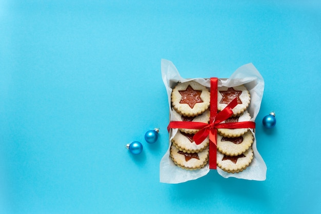 Tradycyjne świąteczne ciasteczka linzer z dżemem w pudełku na niebiesko