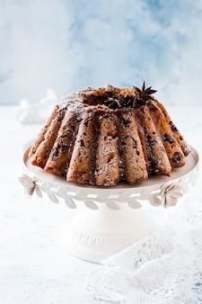 Tradycyjne świąteczne ciasto owocowe, budyń na białej podstawce ceramicznej