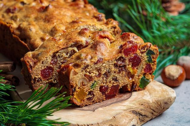 Tradycyjne świąteczne ciasto owocowe na drewnianej desce w świątecznej dekoracji, ciemnym tle.