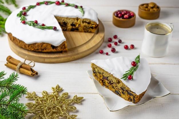 Tradycyjne świąteczne ciasto z owocami, orzechami i białym polewą z dekoracjami i filiżanką kawy