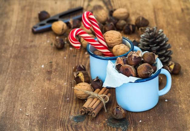 Tradycyjne świąteczne potrawy i dekoracje. pieczone kasztany w niebieskim emaliowanym kubku, orzechy włoskie, laski cynamonu, laski cukierków, szyszka