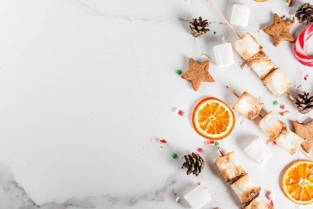 Tradycyjne świąteczne słodycze trzciny cukrowej, ptasie mleczko, suszona pomarańcza, piernikowe gwiazdki, pieczone na ogniu szaszłyki ptasie mleczko na białym marmurze, widok z góry copyspace