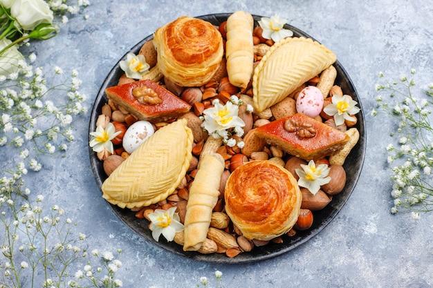 Tradycyjne święto azerbejdżanu ciasteczka novruz baklavas i shakarburas na czarnym talerzu na szarym betonie