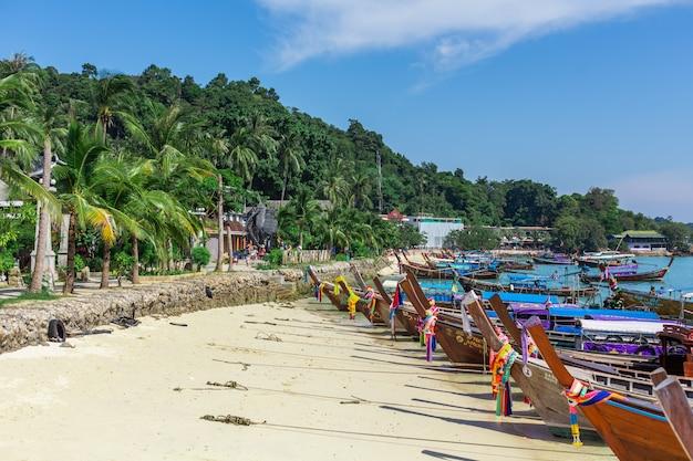 Tradycyjne tajskie drewniane łodzie rybackie owinięte kolorowymi wstążkami. na piaszczystym wybrzeżu tropikalnej wyspy.