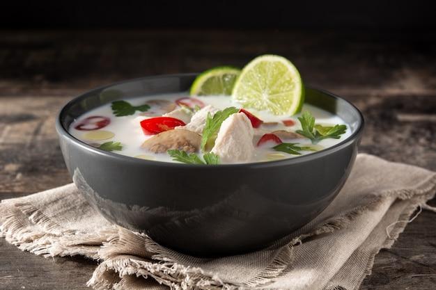 Tradycyjne tajskie jedzenie tom kha gai w misce na drewnianym stole