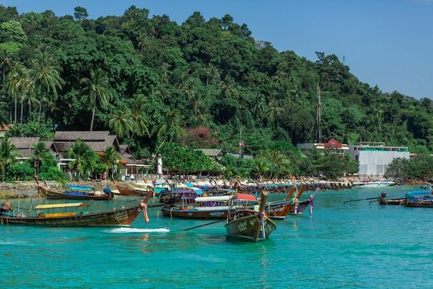 Tradycyjne tajskie łodzie rybackie owinięte kolorowymi wstążkami. na tle tropikalnej wyspy.