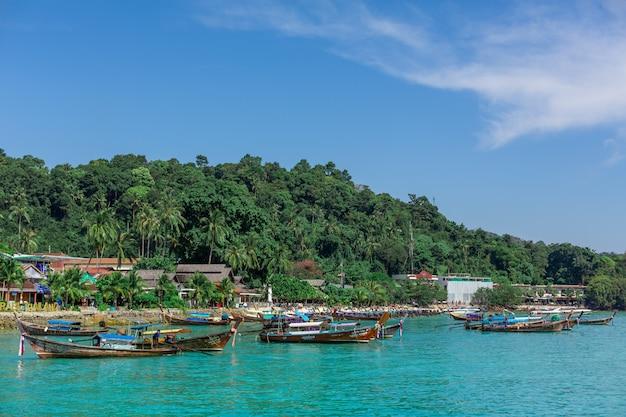 Tradycyjne tajskie łodzie rybackie owinięte kolorowymi wstążkami.