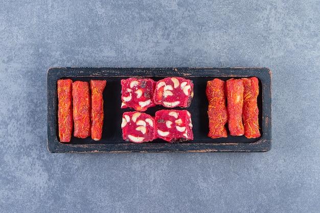 Tradycyjne tureckie przysmaki na drewnianym talerzu na marmurowej powierzchni
