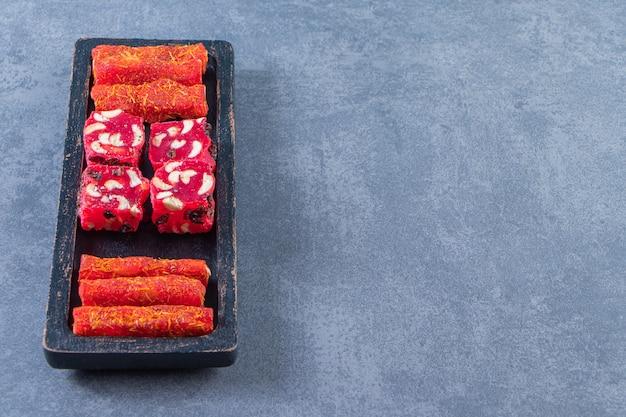 Tradycyjne tureckie przysmaki na drewnianym talerzu, na marmurowym tle.