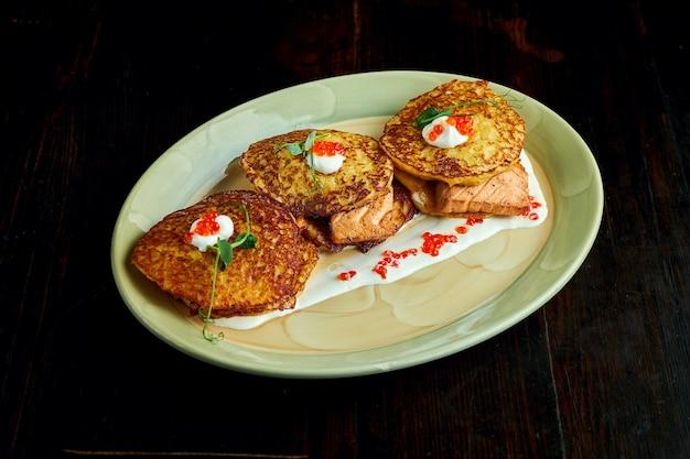 Tradycyjne ukraińskie danie - placki ziemniaczane z łososiem, twarogiem i kawiorem pieczone w piecu, podawane na talerzu